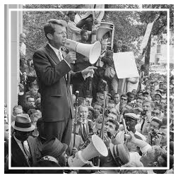 Bobby Kennedy speaking into a megaphone to a crowd.