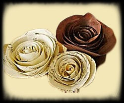 Red paper rose, accompanied by two script, cream colored roses.